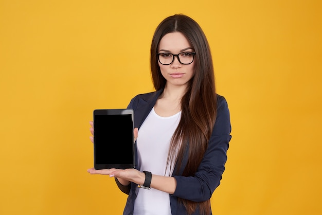 Jeune fille brune à lunettes pose sur jaune.