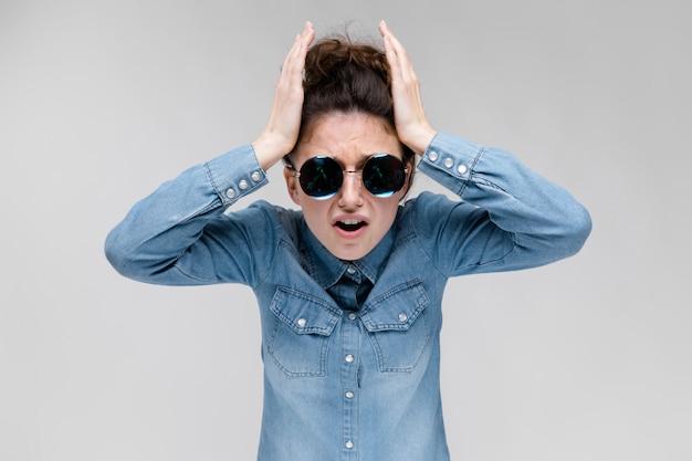 Jeune fille brune à lunettes rondes. les cheveux sont rassemblés en un chignon. la fille tient ses mains derrière sa tête.
