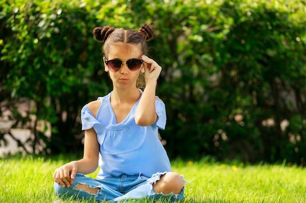 Jeune fille brune à lunettes de soleil assis dans le parc sur l'herbe en été. photo de haute qualité