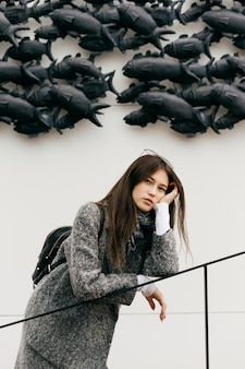 Jeune fille brune en manteau gris à la mode se reposant, marchant dans les rues de la ville et posant, style de rue