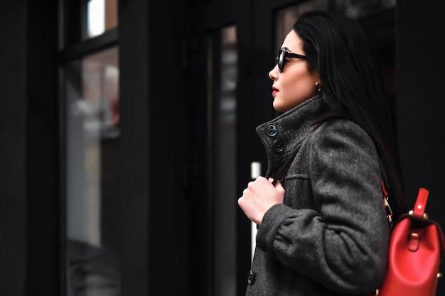 Jeune fille brune marchant dans la rue avec sac à dos rouge