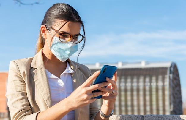 Jeune fille brune avec un masque facial travaillant sur un banc de parc à l'extérieur de son bureau. parler sur son téléphone portable. concept d'entreprise, technologie et télétravail. pandémie de coronavirus.