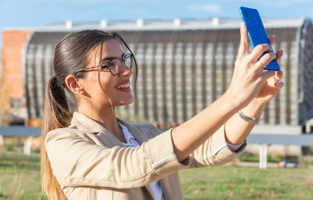 Jeune fille brune avec un masque facial travaillant hors de son bureau faire une photo de soi avec son téléphone portable. concept d'entreprise, technologie et télétravail.