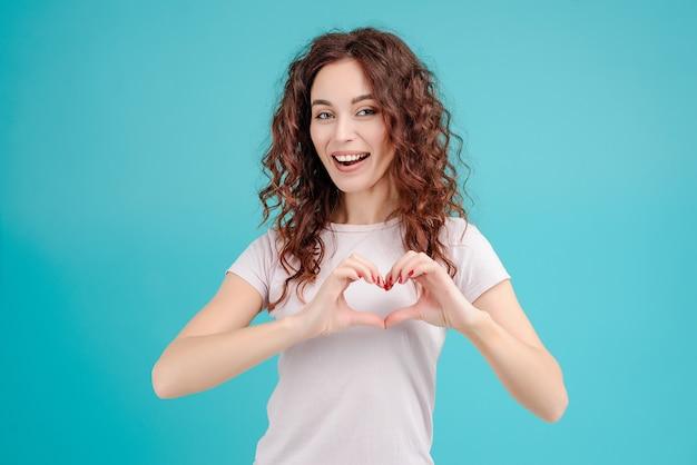 Jeune fille brune montrant le coeur avec ses mains isolées