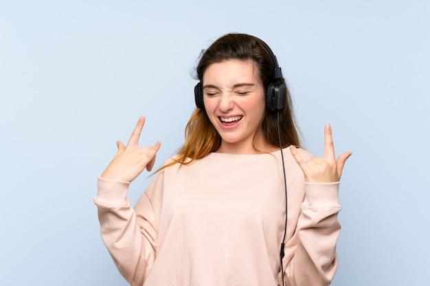 Jeune fille brune sur un mur bleu isolé à l'aide du téléphone portable avec casque et danse