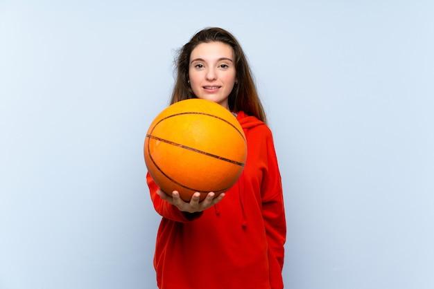 Jeune fille brune sur un mur bleu isolé avec ballon de basket