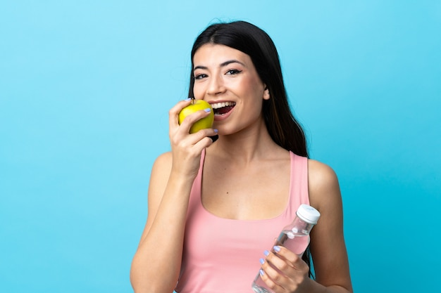 Jeune fille brune sur mur bleu isolé avec une bouteille d'eau et manger une pomme