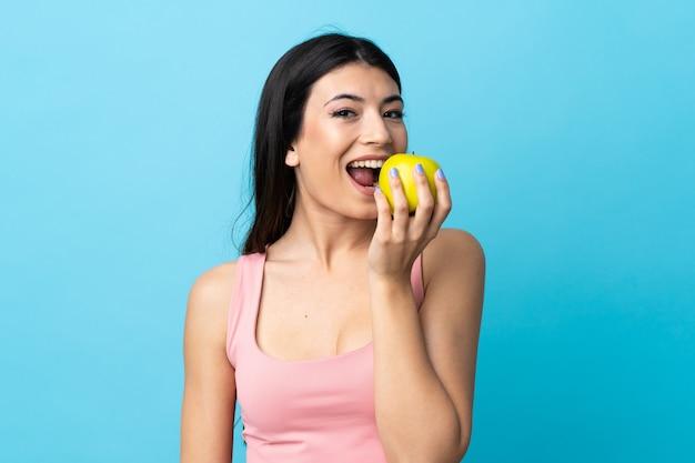 Jeune fille brune sur mur bleu isolé mange une pomme