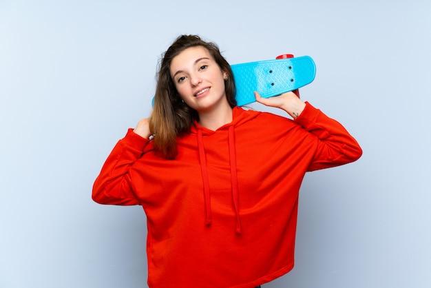 Jeune fille brune sur un mur bleu isolé avec skate