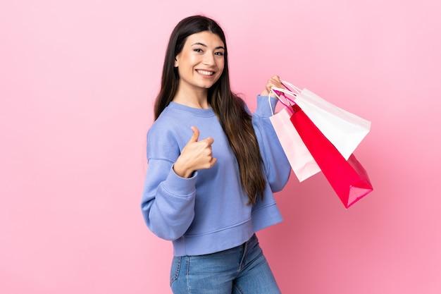 Jeune fille brune sur mur rose tenant des sacs à provisions et avec le pouce vers le haut