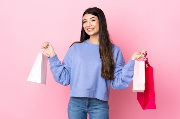 Jeune fille brune sur mur rose tenant des sacs à provisions et souriant