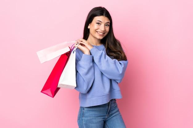 Jeune fille brune sur mur rose tenant des sacs à provisions