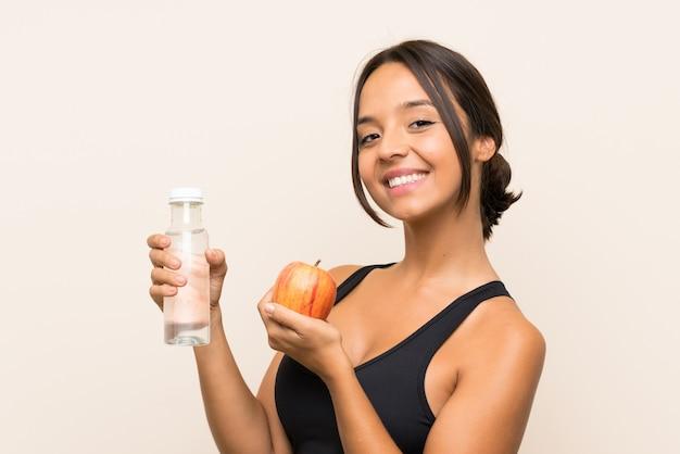 Jeune fille brune avec une pomme et une bouteille d'eau sur un mur isolé