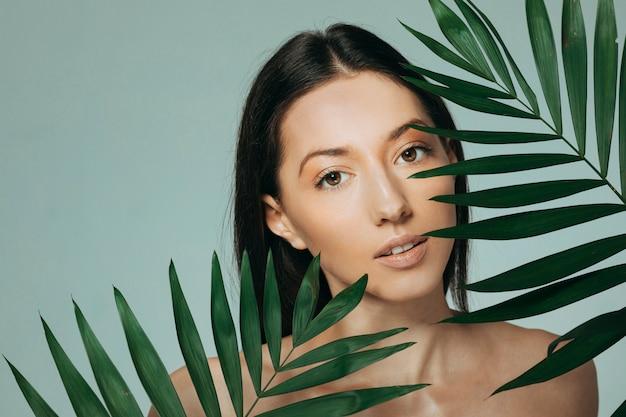 Jeune fille brune posant avec des feuilles exotiques