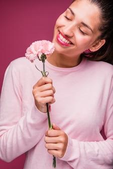 Jeune fille brune posant avec oeillet