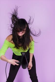 Jeune fille brune posant avec un sèche-cheveux