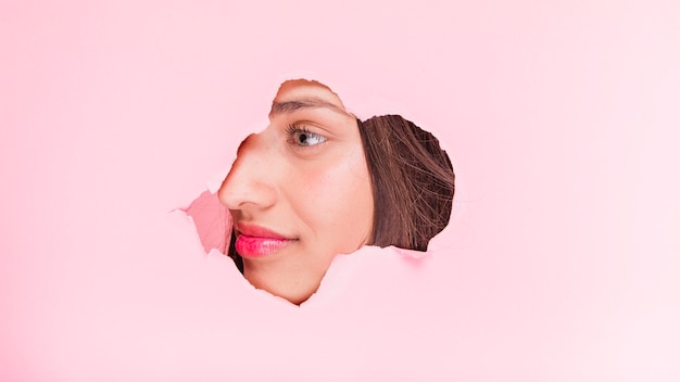 Jeune fille brune posant à travers un trou de papier