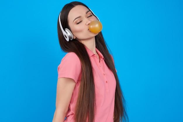 Jeune fille brune pose avec bubble-gum isolé.