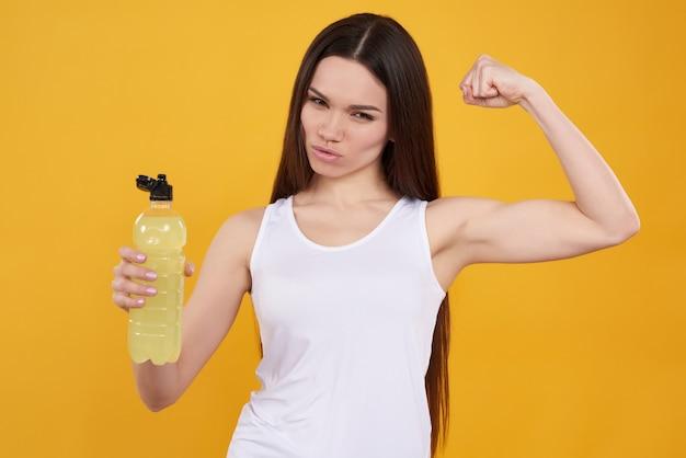 Jeune fille brune pose avec de l'eau sur fond jaune.