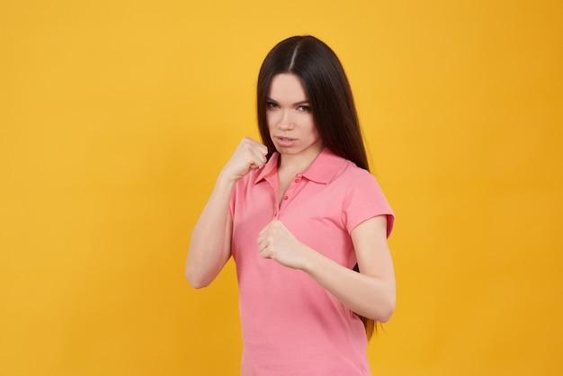 Jeune fille brune pose en position de combat isolé.
