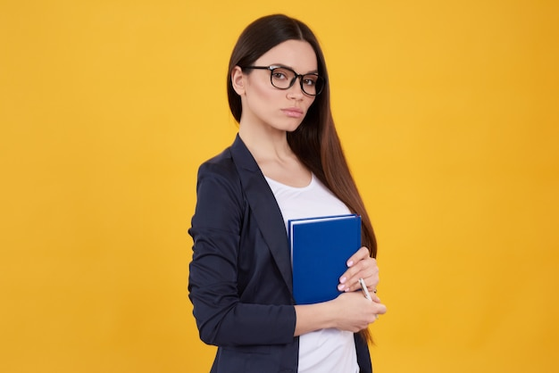 Jeune fille brune pose en prenant des notes