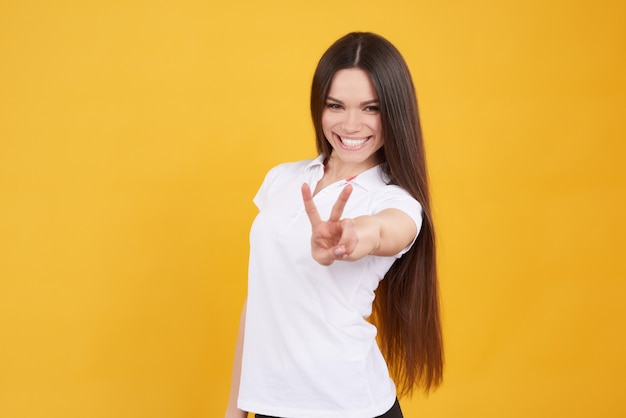 Jeune fille brune pose avec le signe de la victoire isolé.