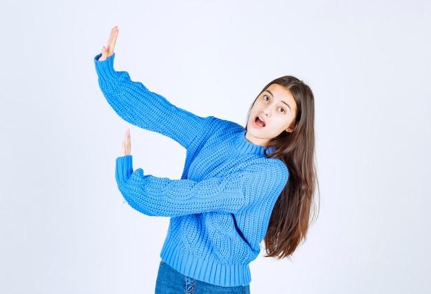 Jeune fille brune en pull bleu disant stop à quelque chose sur blanc.