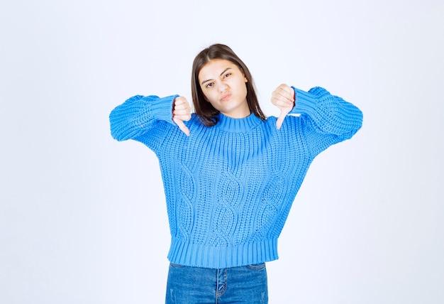 Jeune fille brune en pull bleu donnant les pouces vers le bas sur blanc.