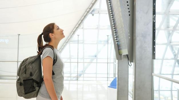 Jeune fille brune avec queue de cheval et gros sac à dos gris portant un t-shirt regarde les horaires de vol dans le salon de l'aéroport