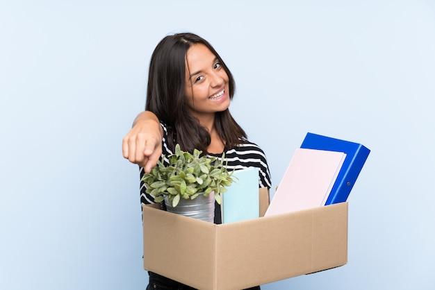 Une jeune fille brune qui bouge tout en ramassant une boîte pleine de choses pointe le doigt vers vous avec une expression confiante