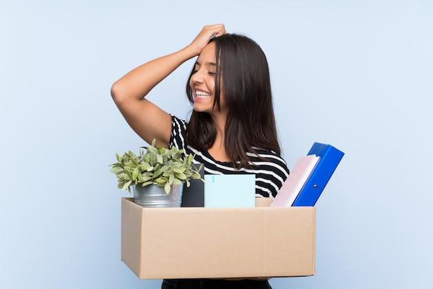 Jeune fille brune qui bouge tout en ramassant une boîte pleine de choses a réalisé quelque chose et dans l'intention de la solution