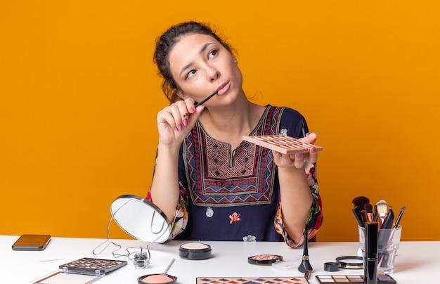 Une jeune fille brune réfléchie assise à table avec des outils de maquillage tenant une palette de fards à paupières et un pinceau de maquillage regardant le côté isolé sur un mur orange avec espace de copie