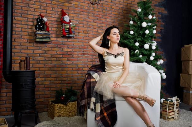 Jeune fille brune en robe posée près du nouvel an des arbres avec une décoration de noël dans la salle de studio de brique.