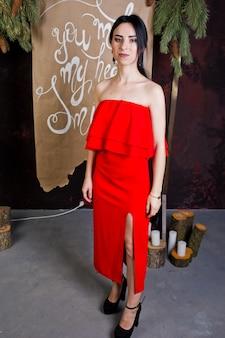 Jeune fille brune en robe rouge posée près de la décoration du nouvel an dans la chambre de studio.
