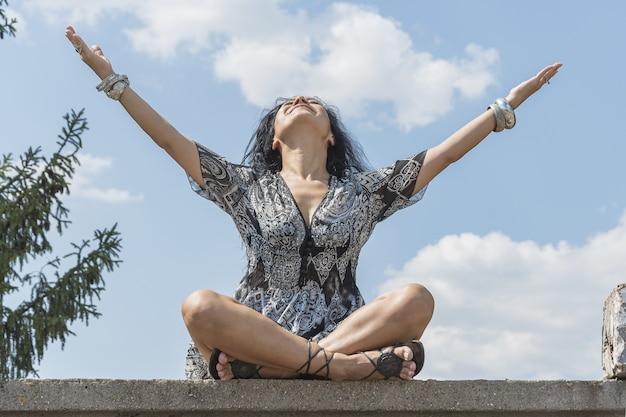 Jeune fille brune s'amusant et se reposant sur les ruines de l'ancien stade de sport