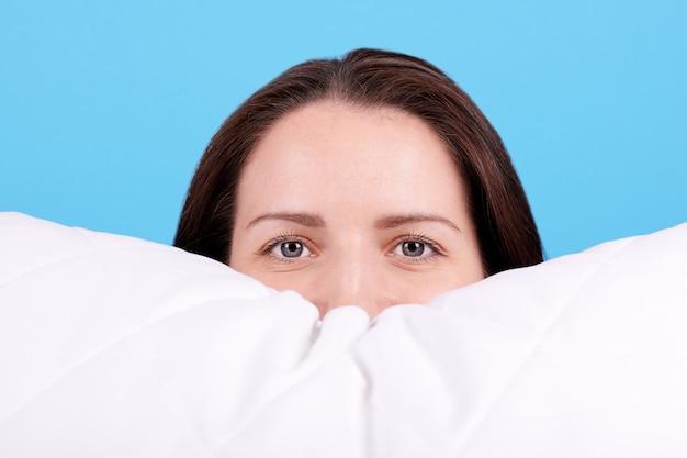 Jeune fille brune se coucha sur un oreiller blanc. isolé sur fond bleu.