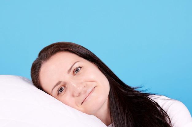 Jeune fille brune se coucha sur un oreiller blanc et sourit. isolé sur fond bleu.