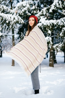 Jeune fille brune séduisante couvrant avec une cape chaude posant dans la forêt de neige
