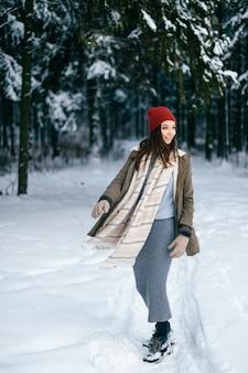 Jeune fille brune séduisante avec une écharpe chaude et un chapeau rouge posant dans la forêt de neige