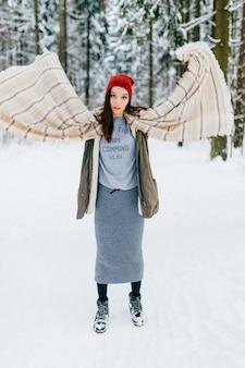 Jeune fille brune séduisante posant avec foulard volant dans la forêt de neige
