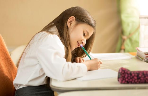 Jeune fille brune souriante en chemise blanche assise derrière le bureau et faisant ses devoirs