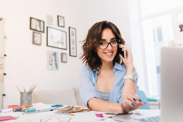Une jeune fille brune souriante dans une chemise bleue travaille dans l'atelier. elle parle au téléphone et tape sur ordinateur. elle sourit à la caméra.