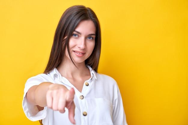Jeune fille brune souriante et pointant vers la caméra, vous choisit isolé sur un mur jaune