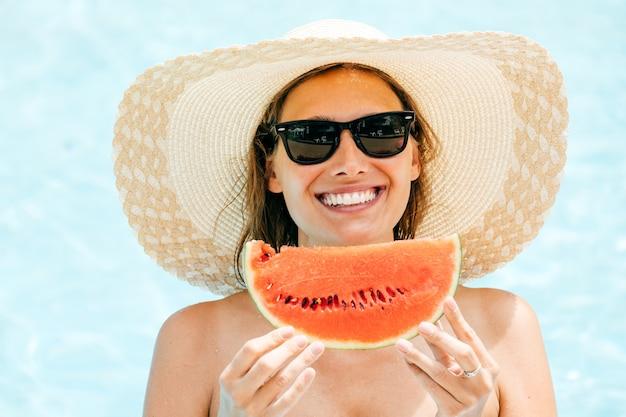 Jeune fille brune souriante tenant une pastèque dans ses mains