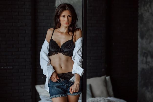 Jeune fille brune en soutien-gorge noir se tient près du lit