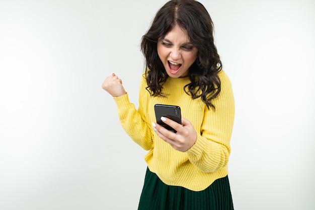 Jeune fille brune surfe sur internet en tenant un téléphone dans ses mains sur un fond blanc isolé