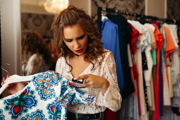 Jeune fille brune surprise en regardant le prix de la robe rouge avec la bouche ouverte.