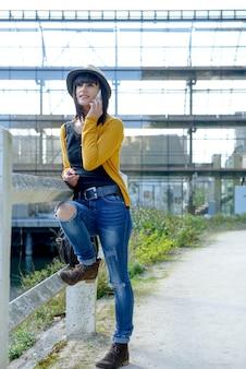 Jeune fille brune avec un téléphone portable dans le parc, à l'extérieur