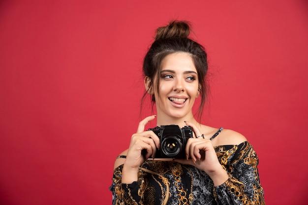 Jeune fille brune tenant un appareil photo reflex numérique professionnel et pensant.