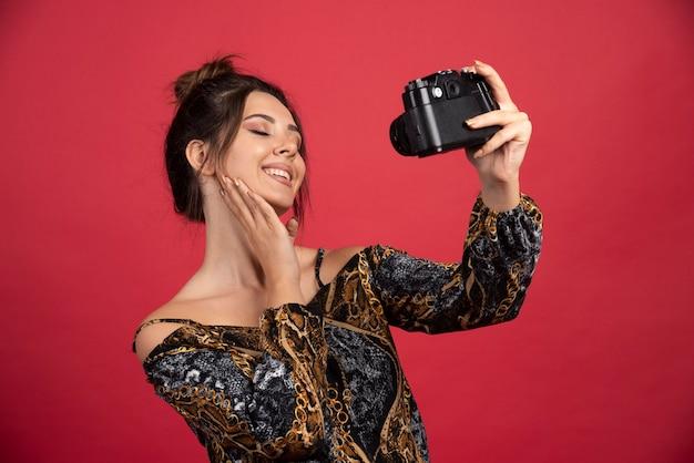 Jeune fille brune tenant un appareil photo reflex numérique professionnel et prend ses selfies joyeux.